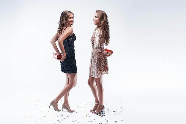 2人の若い女の子の友人が背中の後ろにプレゼントを持って、お互いにプレゼントします。