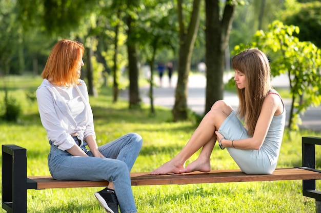 Two young girls friends sitting on a bench in summer park chatting happily having fun.