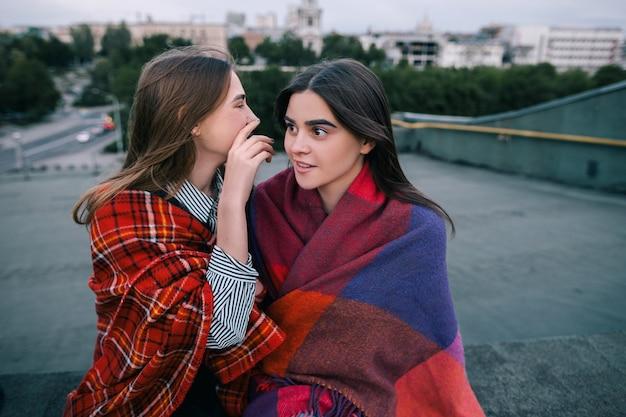 誰かの2人の若い女の子のゴシップ、クローズアップ。一緒に楽しい時間を過ごす、現代の都市生活、コミュニケーションと販売のニュース、秘密と自信の概念