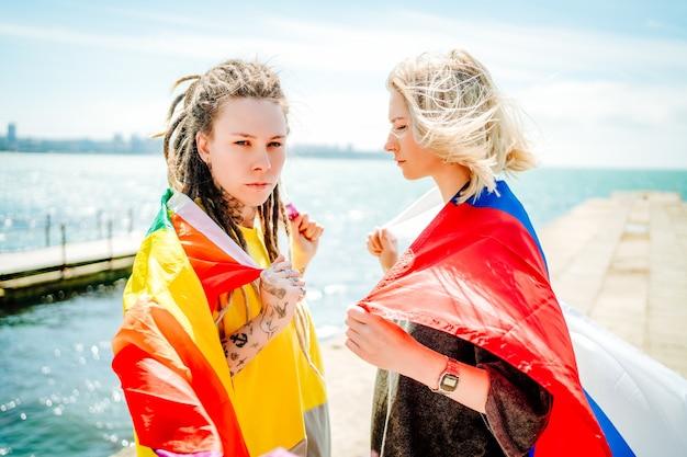 2 人の若い女の子が肩に虹色の旗を持ち、海に面した桟橋にロシアの旗が立っています。高品質の写真