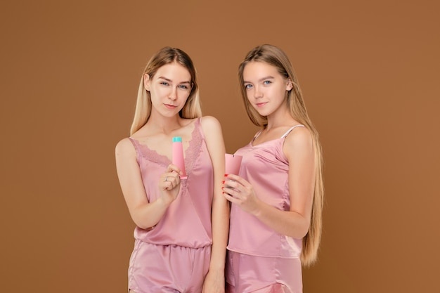 Two young girls holding acne cream in hands