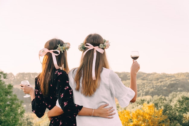 Two young girls hug during sunset in the field with wine glasses friendship concept