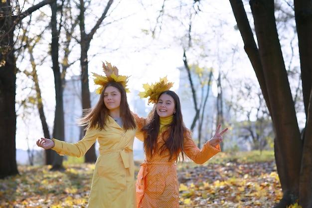 秋の時間の間に秋の公園で二人の若い女の子