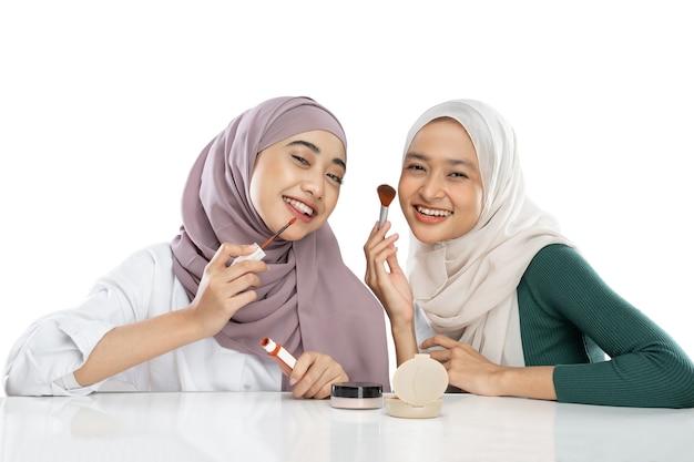 新しい口紅製品をテストするときにブログのビデオを作るベールの2人の若い女の子