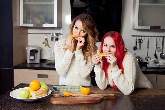 Two young girls in the kitchen talking and eating fruit, healthy lifestyle