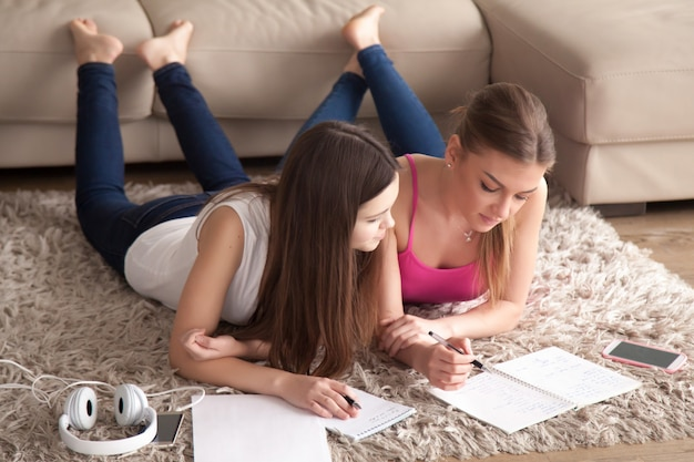 Due giovani ragazze che si trovano sul tappeto, prendendo appunti in blocchetti per appunti.