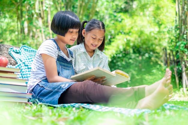 屋外で本を読んで芝生に横たわっている2人の若い女の子