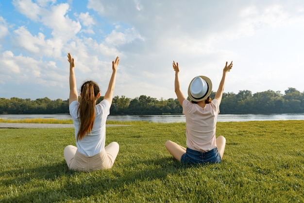 Two young girls meditate in the park near the river, back view