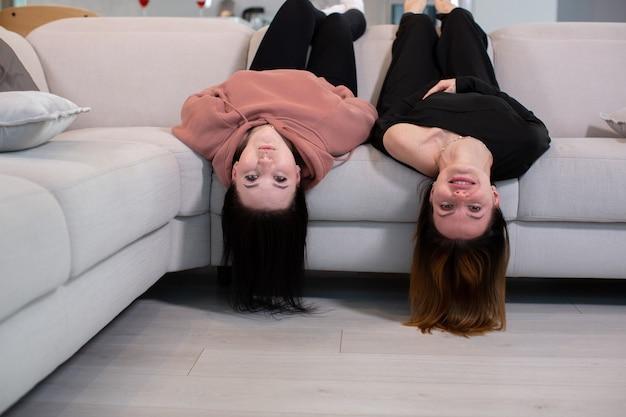 Две молодые девушки весело лежат на диване с поднятыми ногами и смотрят в камеру концепция молодости и дружбы фото высокого качества
