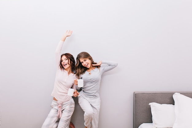 Two young girls in pajamas with cups on grey wall . they stretching and smiling .