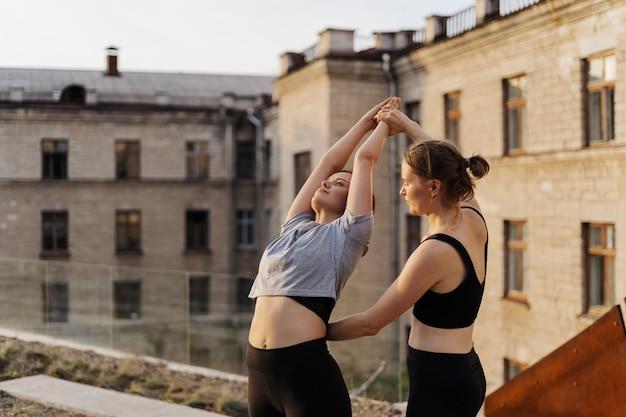 Две молодые девушки занимаются растяжкой и занимаются йогой