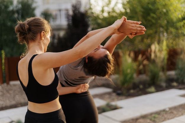 Due ragazze che praticano l'allungamento e l'allenamento di yoga si esercitano insieme