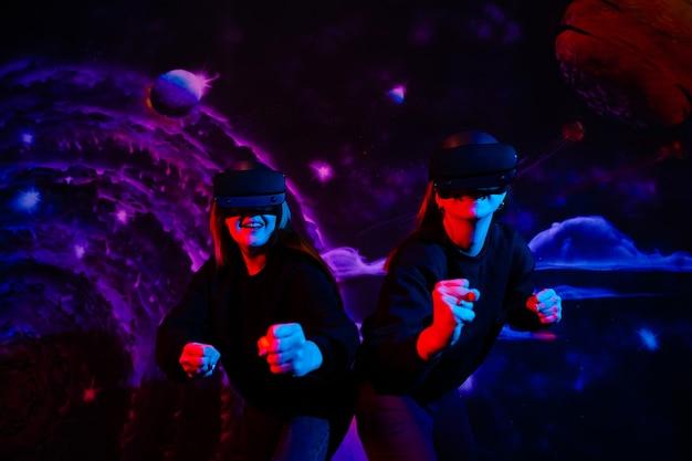 ネオンブルーとレッドライトの高品質の写真で楽しんでいる仮想メガネと2人の若い女の子の姉妹の友人