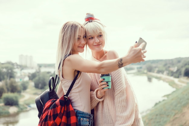 Two young girls sisters posing on the street, make selfie