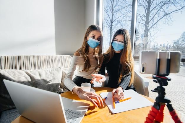 Две молодые девушки сидят в кафе в масках и ведут видеоблог