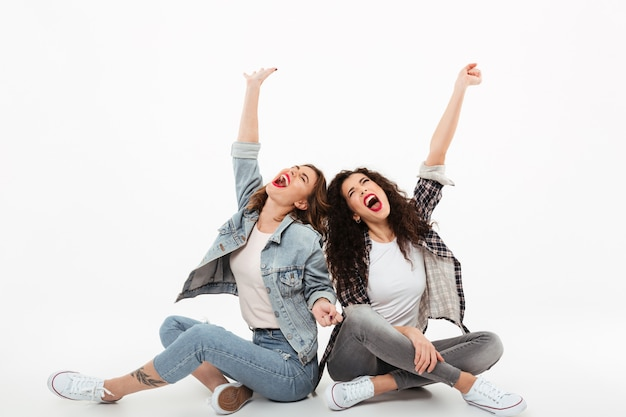 Two young girls sitting on the floor together while screaming and looking up over white wall