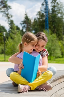 Две молодые девушки сидят на скамейке на открытом воздухе и читают книгу