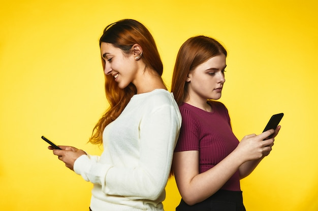 Two young girls stand back to back and look in their phones standing