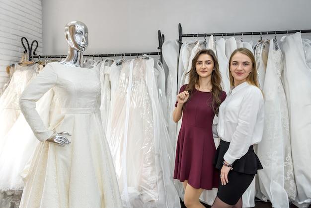 Две молодые девушки стоят возле манекена в свадебном магазине