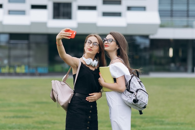 Two young girls taking selfie self portrait photos on smartphone.female showing positive face emotions