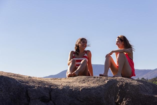 화창한 날 바위 위에서 이야기하고 웃고 있는 두 어린 소녀. 친구. 공간을 복사합니다. 선택적 초점입니다.