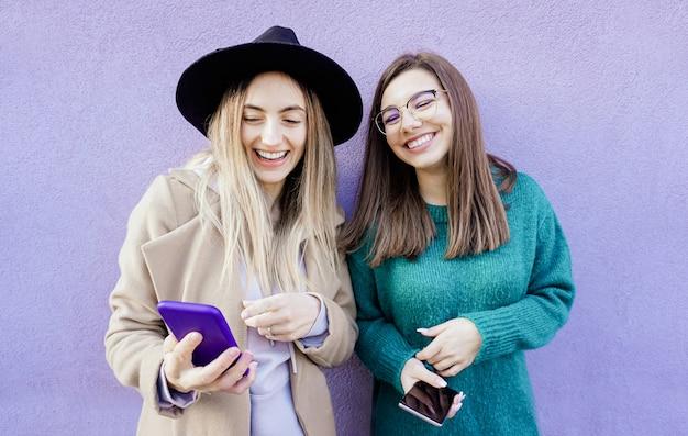 Две молодые девушки с помощью своего смартфона