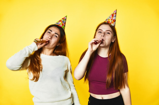 Two young girls wearing birthday hats stand