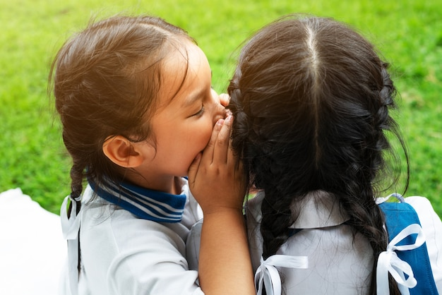 Two young girls whispering and sharing a secret during playground