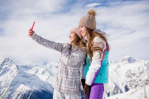 Two young girls in winter clothes take selfies on the background of snowy mountains
