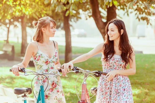 Two young girls with bicycles in park Free Photo