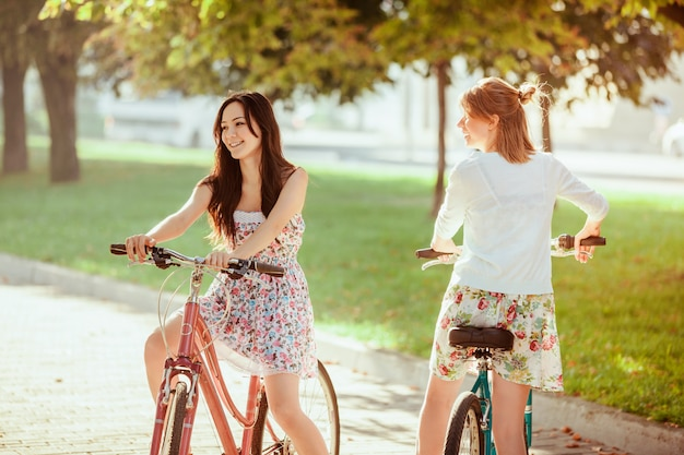 Two young girls with bicycles in park