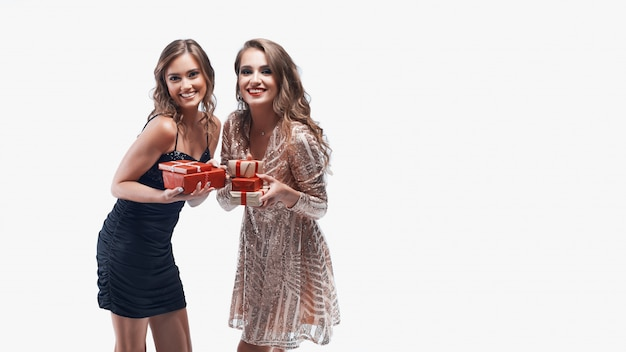 Two young girls with red presents in hands isolated on white