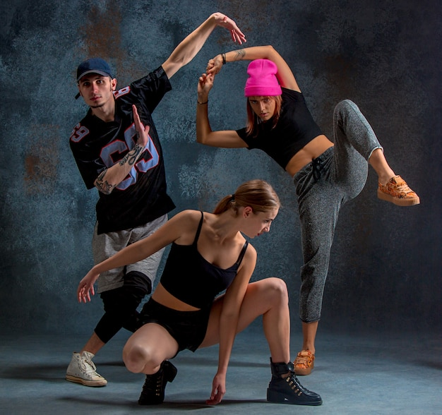 Two young girsl and boy dancing hip hop in