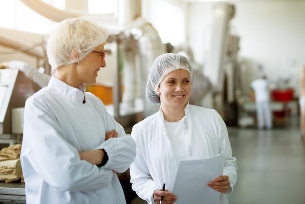 Две молодые великолепные работницы беседуют, а одна из них хранит документы со статистикой.