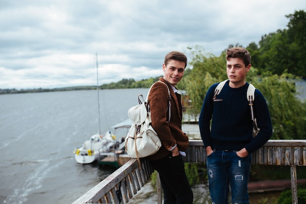 Двое молодых парней стоят на пристани и один из них повернул голову