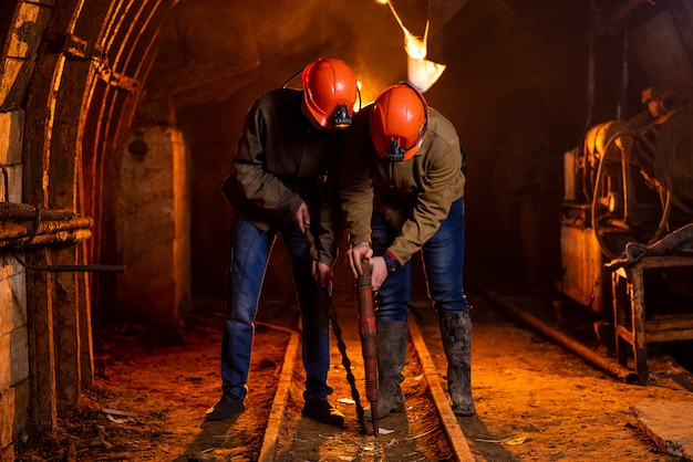 Two young guys in a working uniform and protective helmets, carry out work in the mine