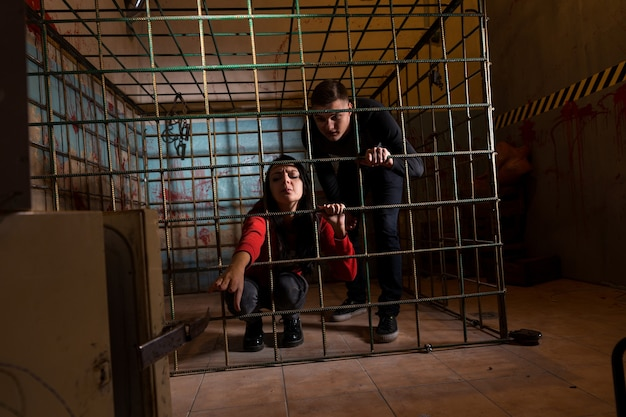 Two young halloween victims imprisoned in a metal cage with a blood splattered wall behind them, girl pulling her hand through the bars and trying to get out