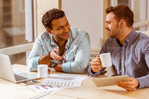 Two young handsome businessmen in casual clothes smiling.