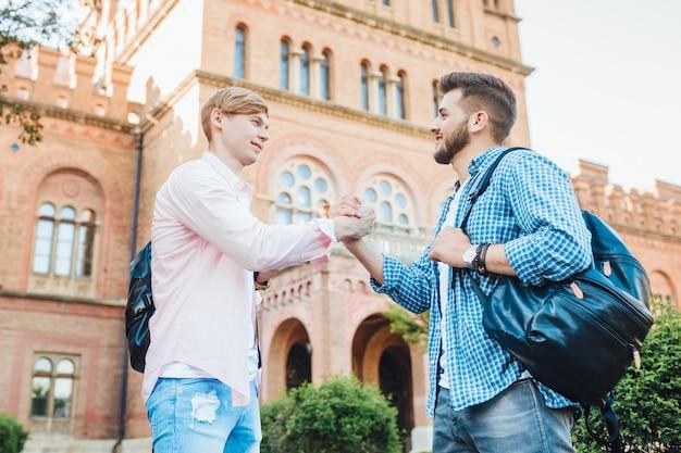 Два молодых симпатичных парня студентов с рюкзаками приветствуют друг друга на территории кампуса. в университете.