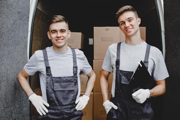 箱だらけのバンの前に制服を着た2人の若いハンサムな笑顔の労働者が立っている