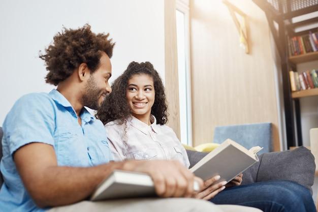 Молодой красивый студент 2 в вскользь одеждах сидя на софе в яркой современной библиотеке после исследования, усмехаться, говорить, читать книги, ища информацию для проекта команды градации.