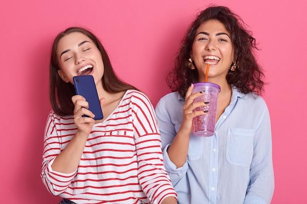 Две молодые счастливые и взволнованные кавказские девушки поют вместе онлайн караоке-песню с телефоном и коктейлем, как микрофон