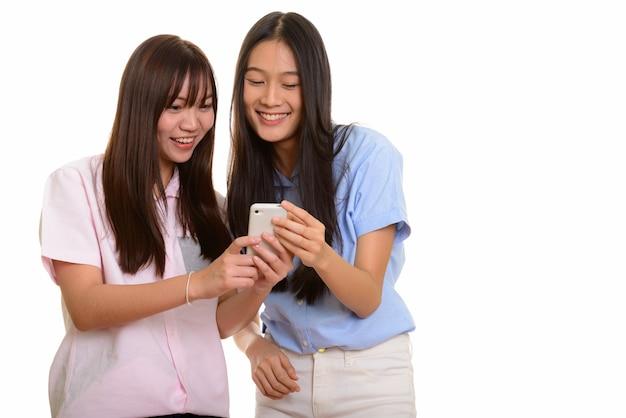 Две молодые счастливые азиатские девочки-подростки улыбаются и используют мобильный телефон
