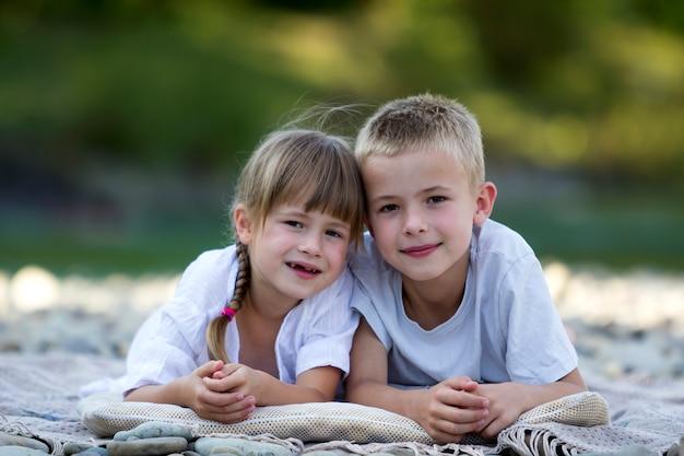 2 молодых счастливых милых белокурых детства, мальчик и девушка, брат и сестра кладя на галечный пляж на запачканный яркий солнечный летний день. дружба братьев и сестер, досуг и идеальный праздник концепции.