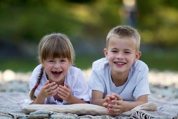Две молодые счастливые милые белокурые дети, мальчик и девочка, брат и сестра лежат на галечном пляже на размытой яркой