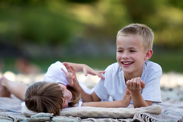 Два молодых счастливых милых белокурых смеющихся ребенка, мальчик и девочка, брат и сестра веселятся на галечном пляже на затуманенное яркое солнечное лето. дружба и идеальный праздник концепции.