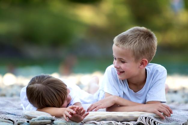 2 молодых счастливых милых белокурых смеясь над детей, мальчик и девушка, брат и сестра имея потеху на галечном пляже на запачканной яркой солнечной предпосылке bokeh лета. дружба и идеальный праздник концепции.