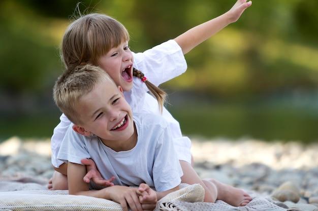 Два молодых счастливых милых белокурых смеющихся ребенка, мальчик и девочка, брат и сестра, весело проводящие время на галечном пляже на стертом ярком солнечном летнем bokeh. дружба и идеальный праздник концепции.