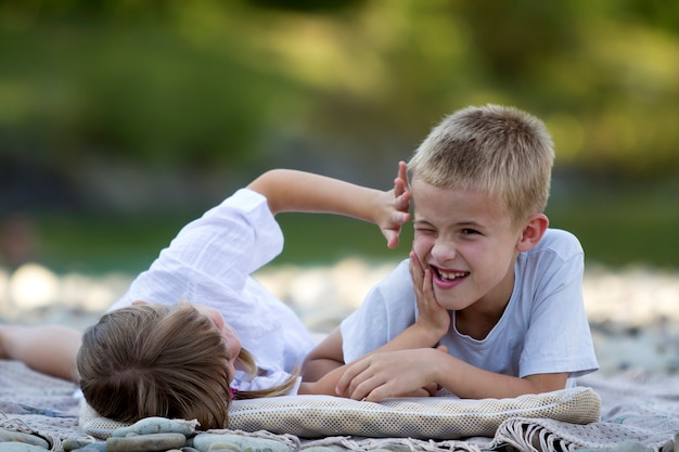 Два молодых счастливых симпатичных белокурых смеющихся ребенка, мальчик и девочка, брат и сестра веселятся на галечном пляже