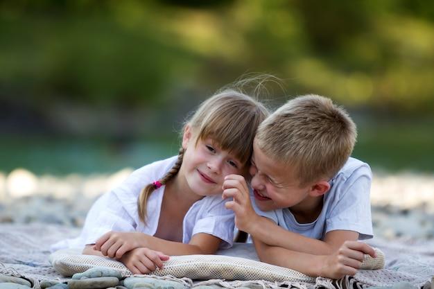 Кладка 2 молодых счастливых милых белокурых усмехаясь детей, мальчика и девушки, брата и сестры обняла на галечном пляже на запачканной яркой солнечной предпосылке летнего дня. дружба и идеальный праздник концепции.